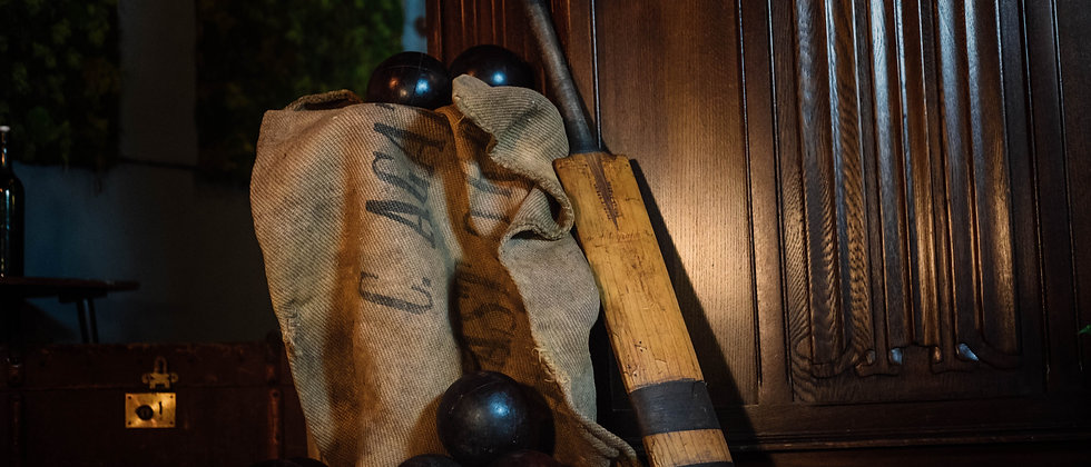 A close up of an antique garden game selection. A 1930's boules set and vintage cricket bat