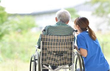 車いすの老人と介護者