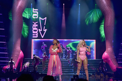 Nicki Minaj and Ariana Grande in front of giant inflatable legs