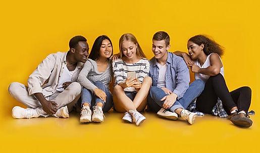 teenagers-sitting-floor-looking-smartpho