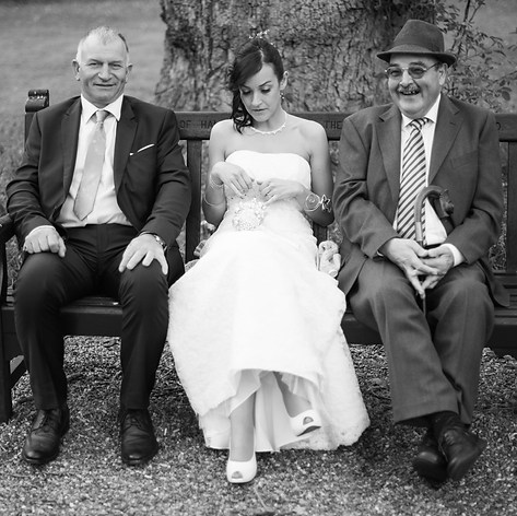 """A London bride is sitting on a bench with her father and her father in law on each side, laughing, captured by Aurélie """"Photobya4"""" Four"""