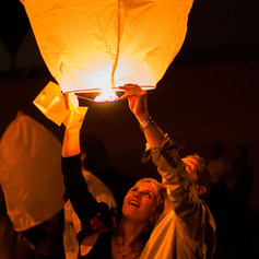 """a couple look up whilst launching a Chinese lantern during the evening of a wedding in France captured by Aurélie """"Photobya4"""" Four"""