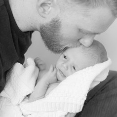 "A father kisses the forehead of his newborn son captured by Aurélie ""Photobya4"" Four"