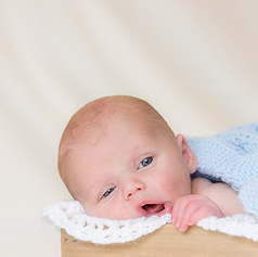 A cute newborn baby is pictured with a blue blanket in a wooden box