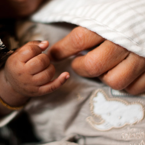 """A baby holds the hand of his grandfather captured by Aurélie """"Photobya4"""" Four during a family session"""