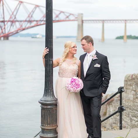 """Karen and Justin pose for a wedding portrait after their civil ceremony at Orocco Pier with the Forth Bridge in the backdrop in Scotland, captured by Aurélie """"Photobya4"""" Four"""
