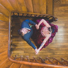 """A couple of newly weds pose and make a heart shape with their arms, looking up in a staircase. captured by Aurélie """"Photobya4"""" Four"""