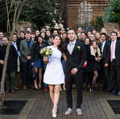 A newly wed couple poses for an informal group picture with their guests after their micro ceremony in London