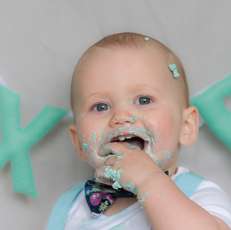 """Baby Dexter is smiling, face covered in cake frosting during his """"cake smash"""" photography session captured by Aurélie """"Photobya4"""" Four for his first birthday"""