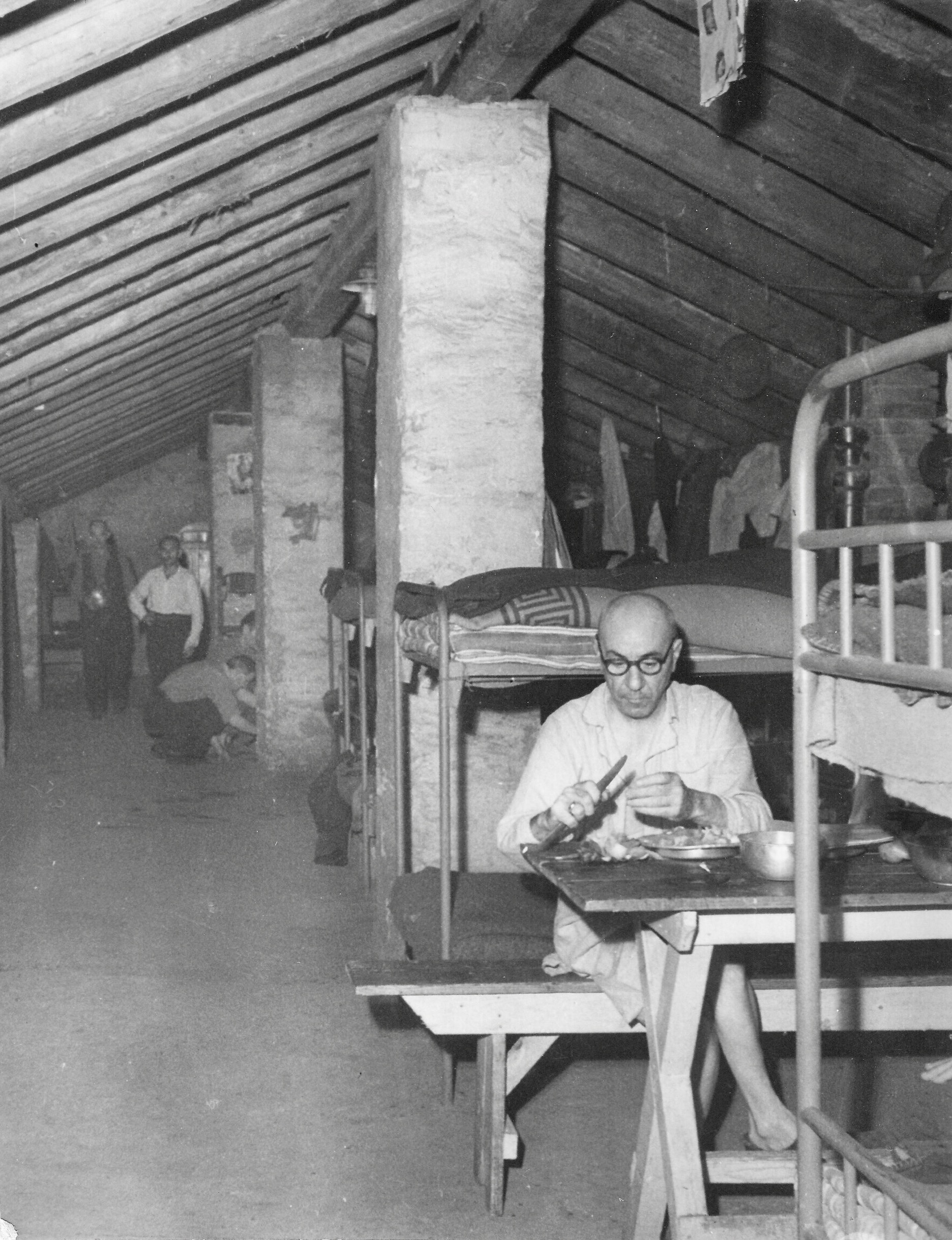 Gesuiti camp, attic, Russian refugee prepares bread and onions meal 1950-51