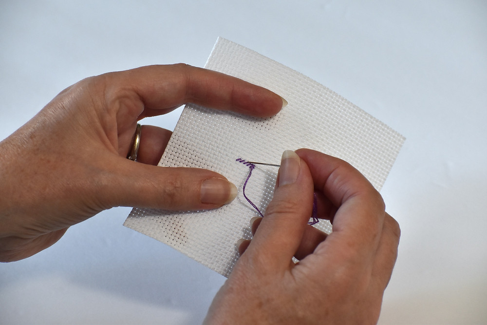 Rhona works to finish a line of purple cross stitches on square aida fabric.