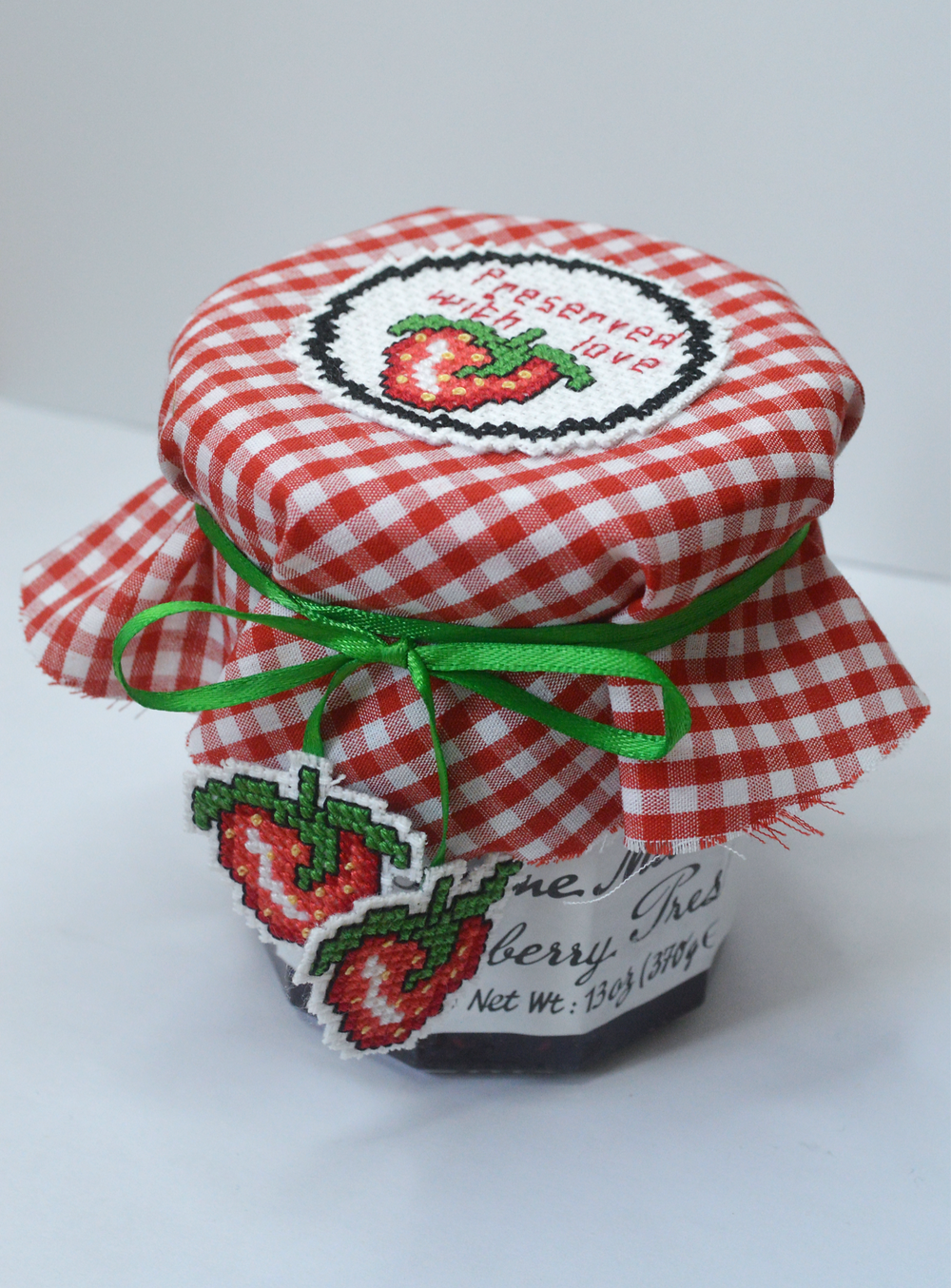 A jam jar with a red gingham cover.