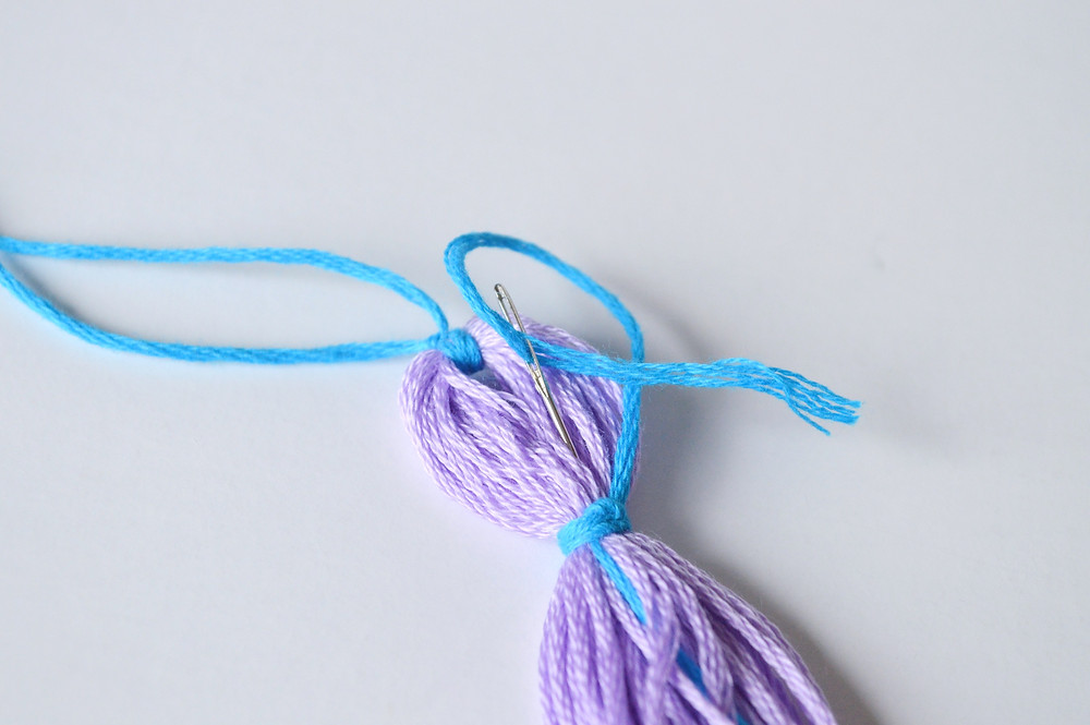 A purple skein of DMC floss has an embriodery needle inserted into it as it is made into a tassel.