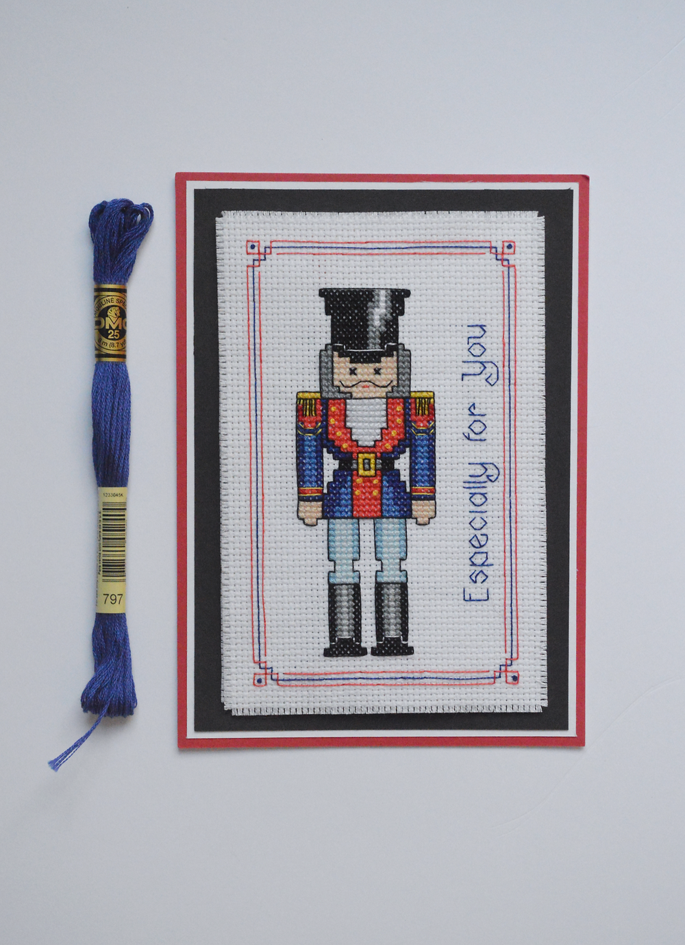 Cross stitched card next to a skein of blue DMC thread