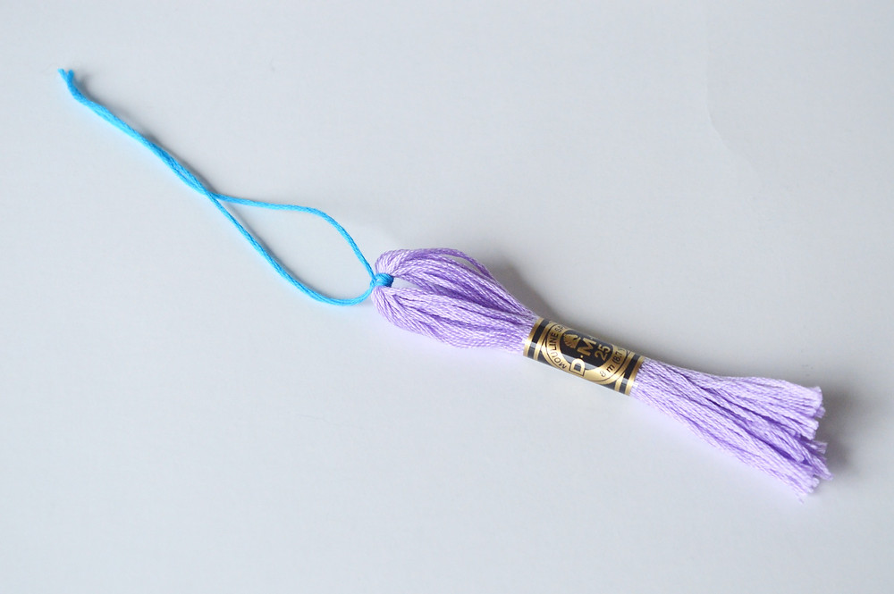 A purple skein of DMC floss has a blue thread attached to it.