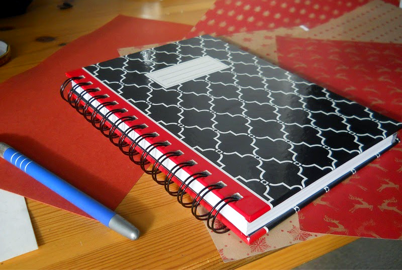 A notebook lays on a wooden table covered in construction paper.