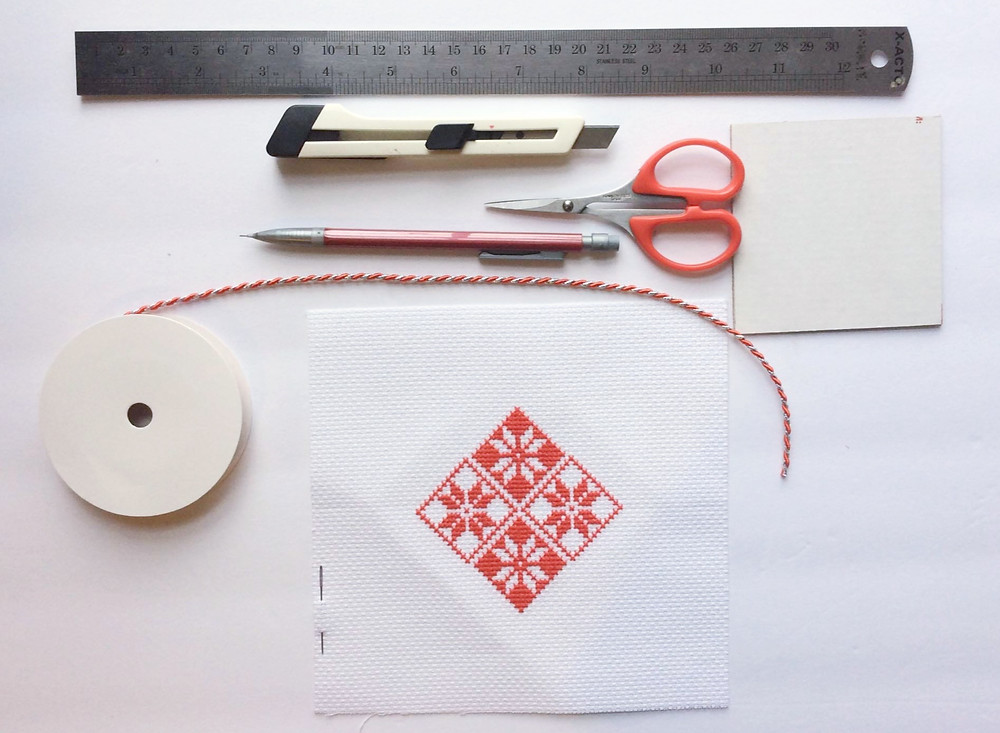 A Christmas cross stitch design sits next to supplies needed to make the design into a Christmas tree ornament.