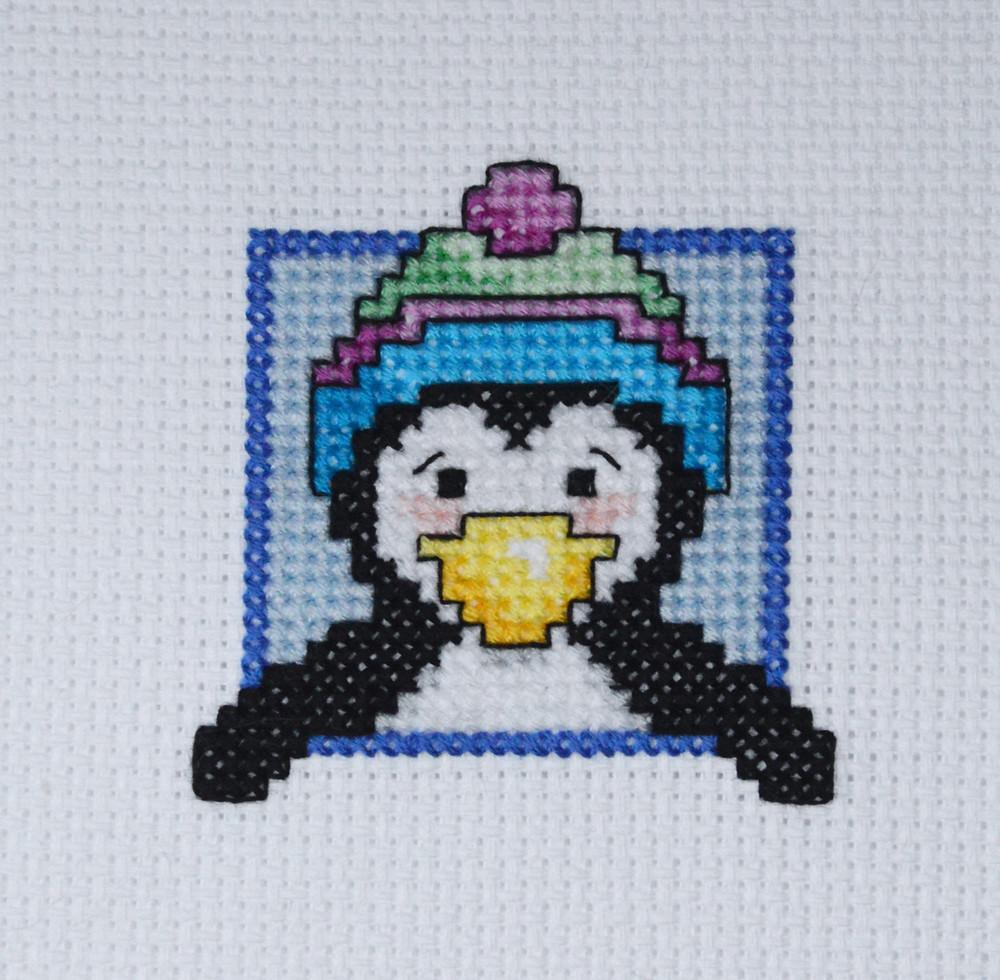 cross stitch penguin wearing a bauble hat