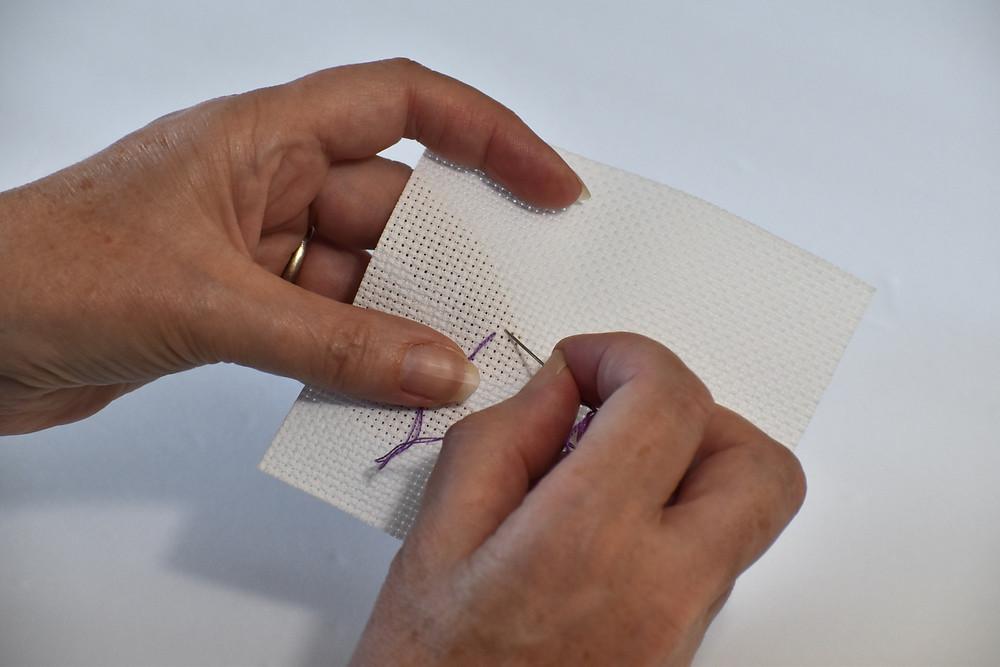 Rhona pulls her purple thread through the aida cloth.