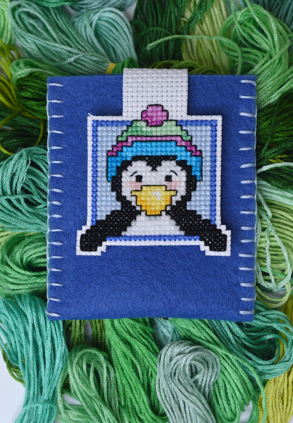 A cross stitch penguin gift tag holder.