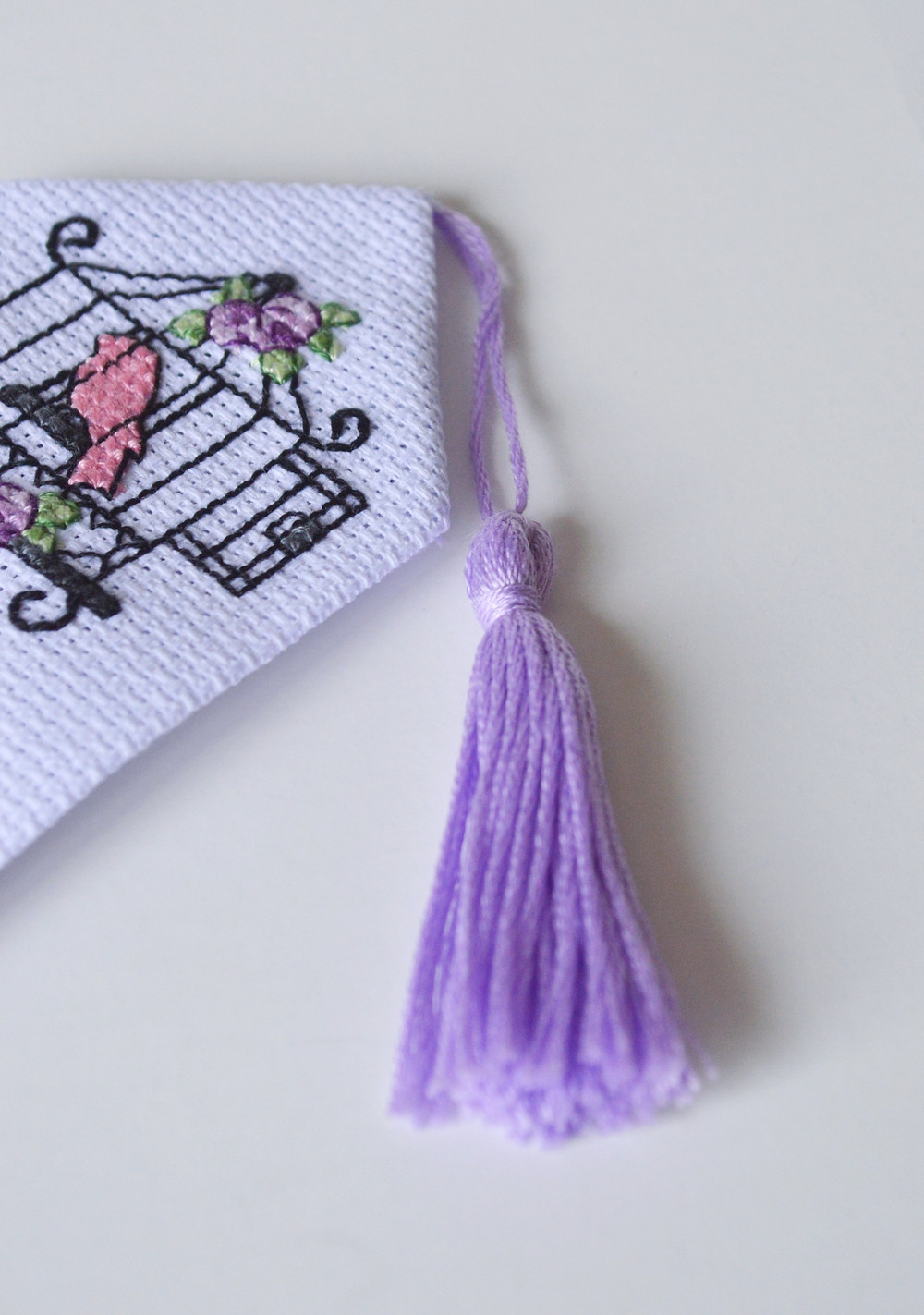 A cross stitch bookmark sits on a table. At the top end of the aida fabric, a purple tassel is attached.