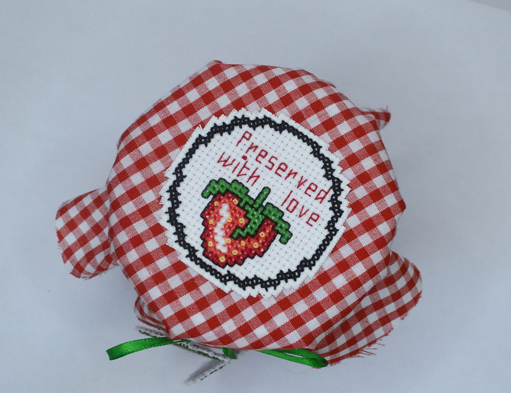 cross stitch on top of red gingham cover on a jam jar