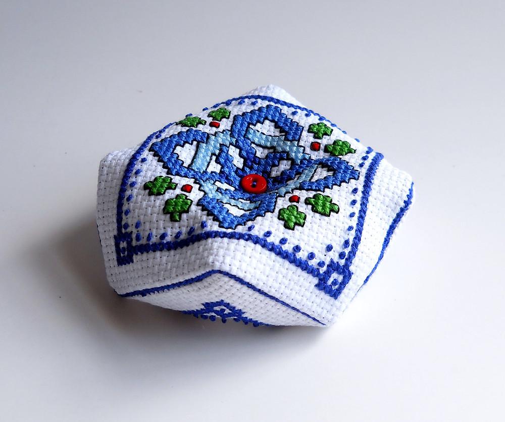 cross stitched biscornu in shades of blue thread