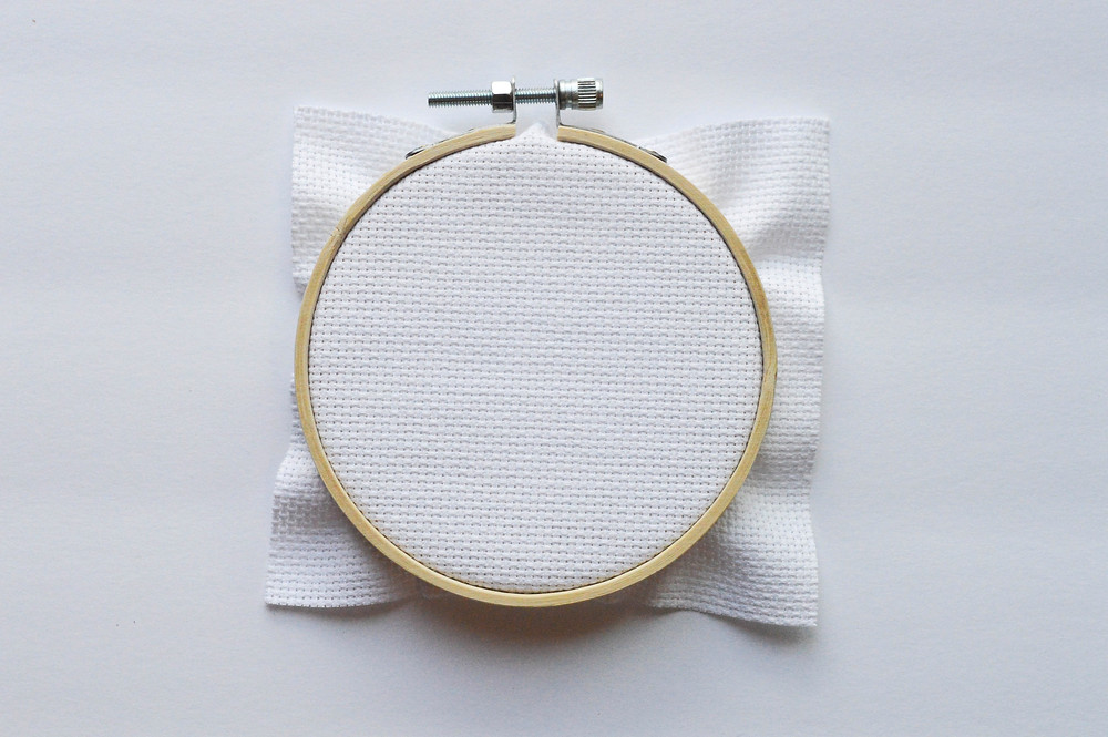 A cross stitch embroidery hoop sits against a white background