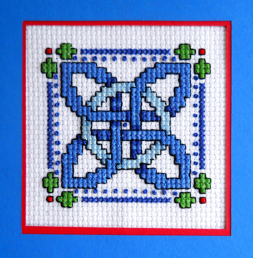 Celtic knot cross stitch design in shades of blue
