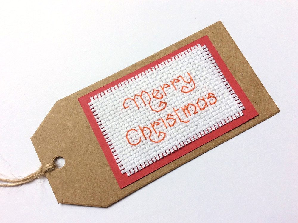 brown card gift tag with cross stitched greeting attached to it