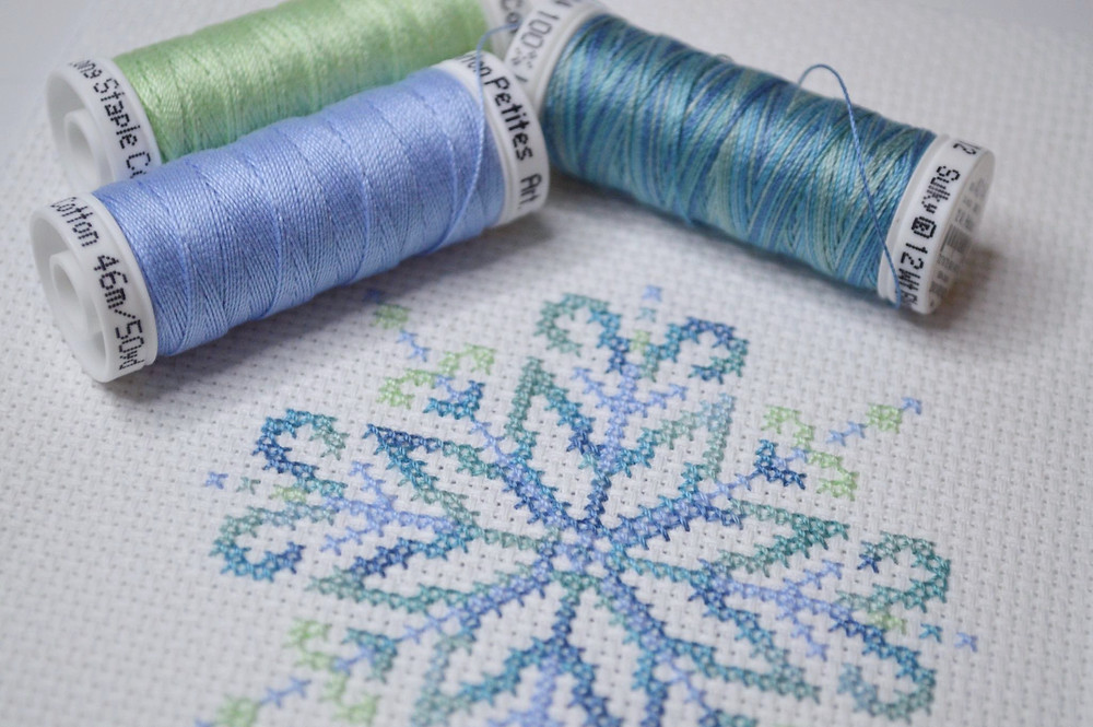 close up of cross stitched snowflake design with sulky threads used to stitch it