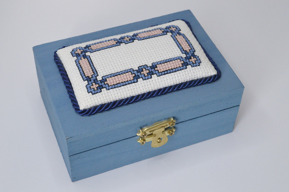 A cross stitch design is attached to a keepsake box.