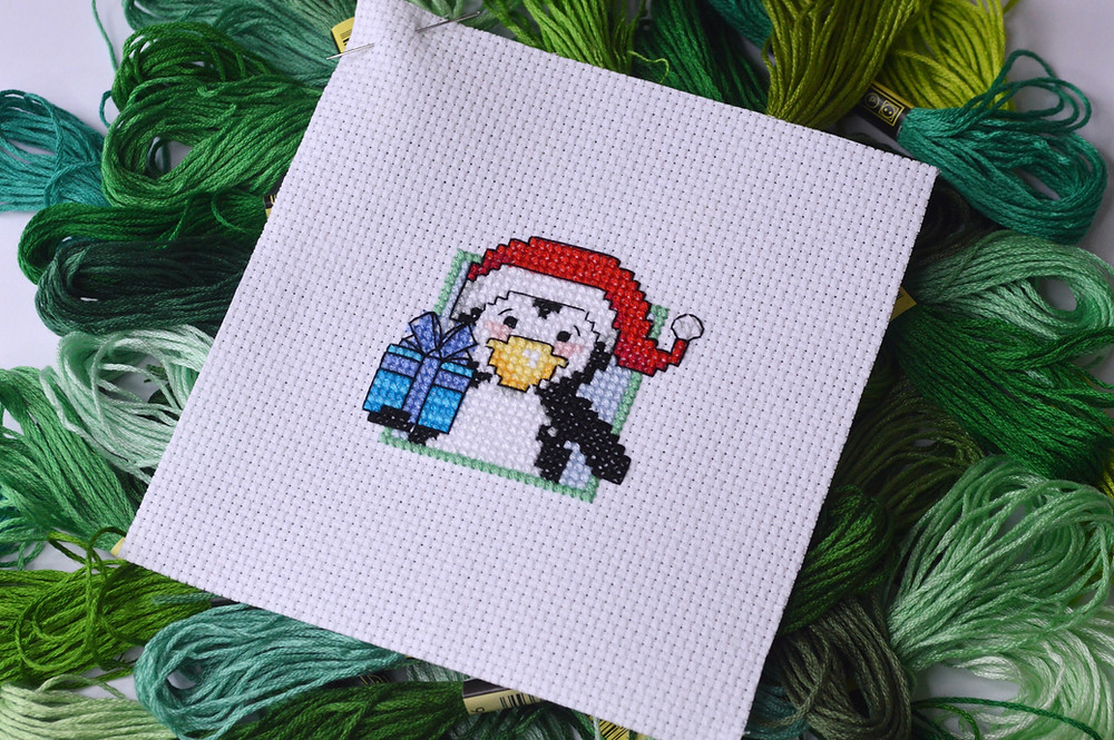 Cross stitched penguin holding a present.
