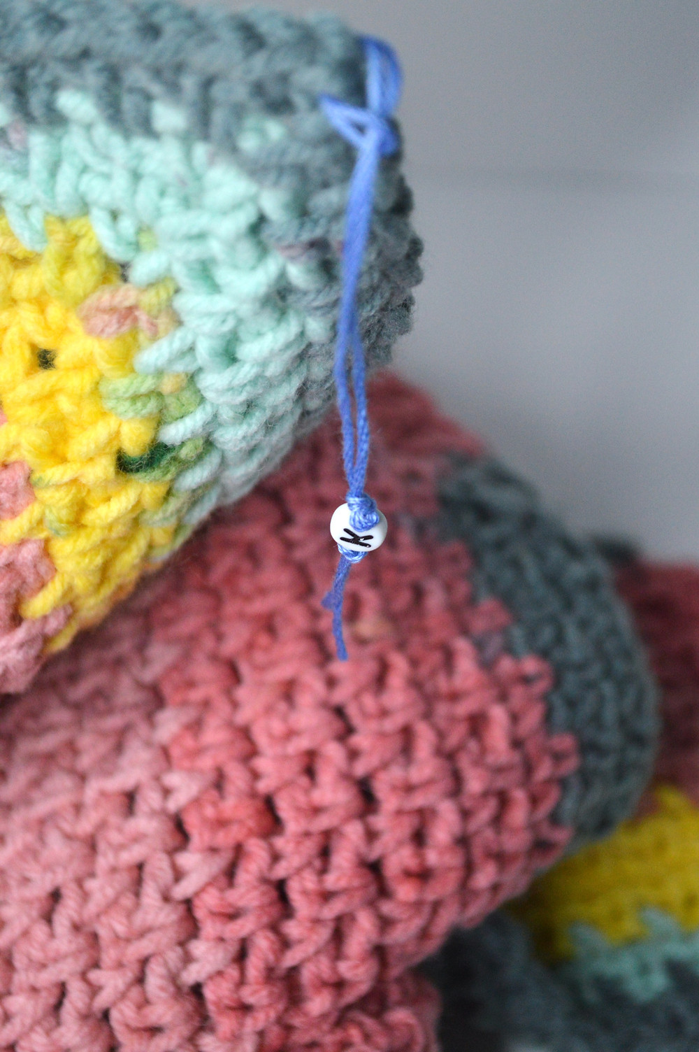A crocheted shawl in pinks, blues, and yellows.