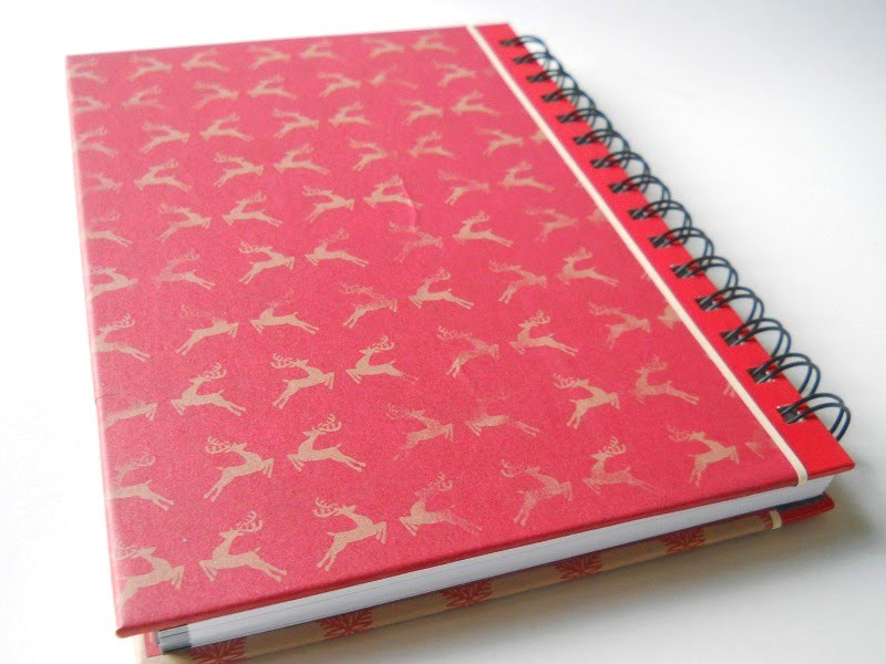 A notebook covered in red paper with gold reindeer lays on a white surface.