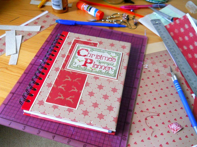 "A notebook with a red and green ""Christmas Planner"" cross stitch design sits on a table covered in crafting supplies such as glue sticks, embroidery scissors, and paper.,"