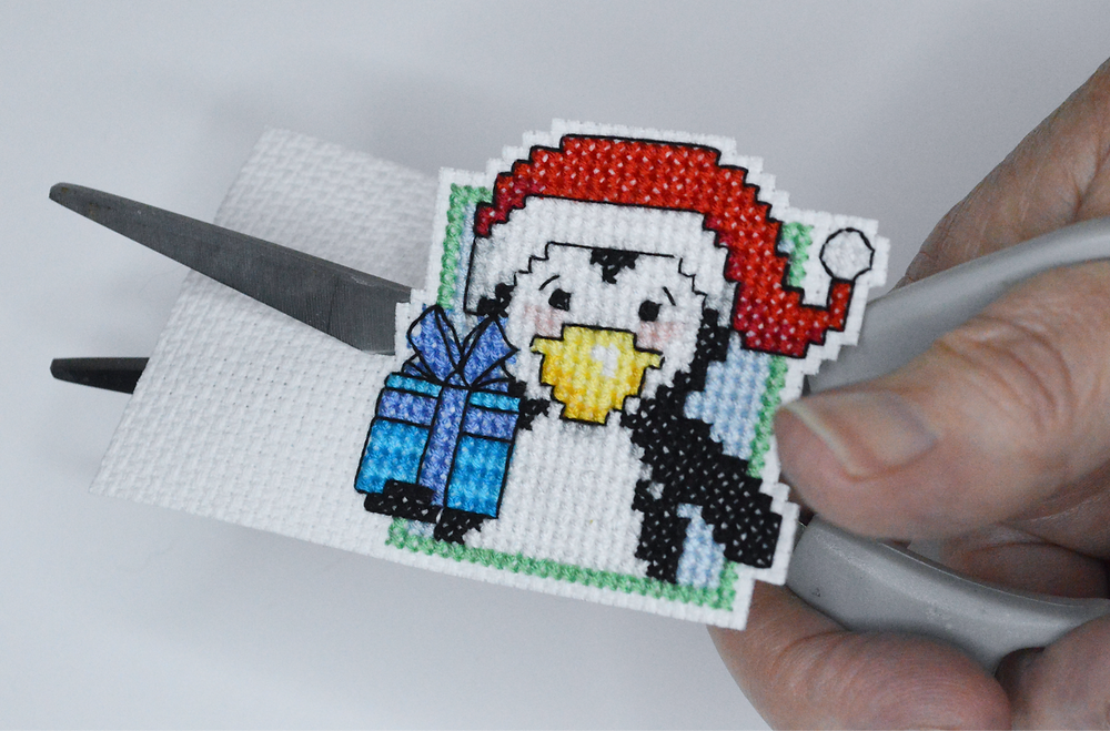Cross stitched penguin holding a present, stitched on aida fabric.