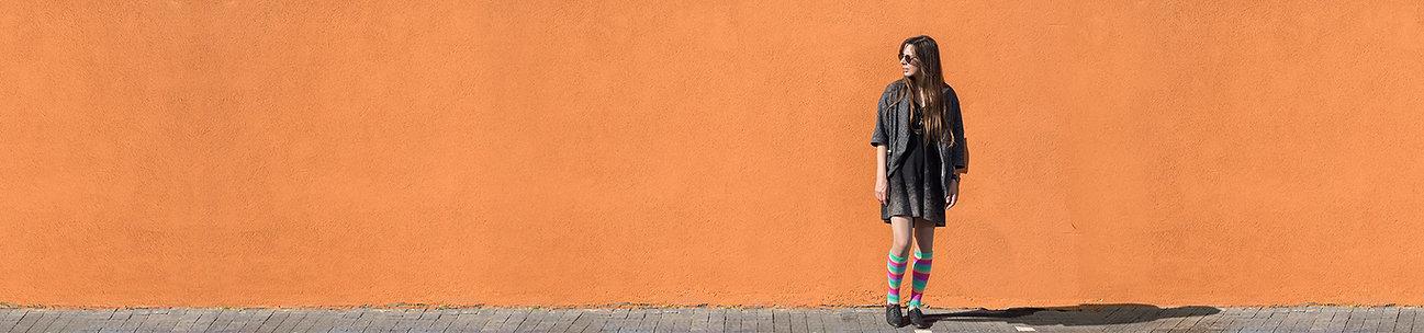 Vrouw die zich tegen oranje muur