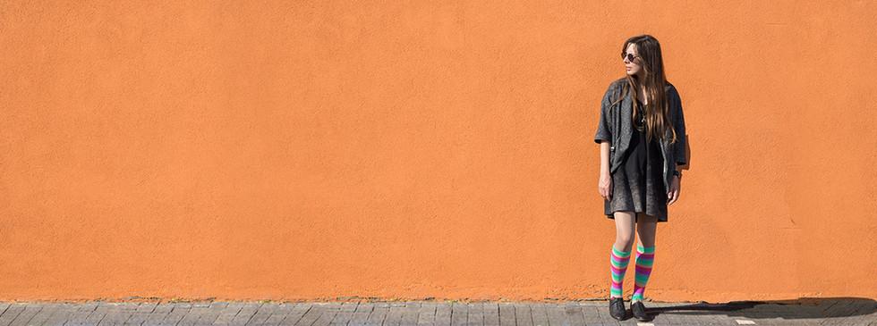 Femme debout contre le mur d'orange