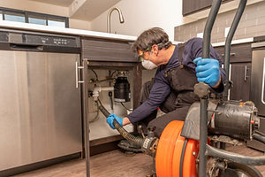 Drain cleaning by professional plumber wearing a safety mask, using an auger.jpg