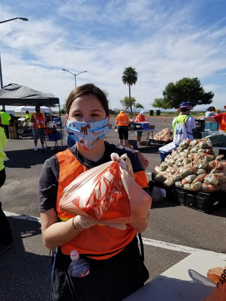Student from Mohave High School FCCLA ECE Chapter holds up a bag of fresh produce .  6000 bags of produce were distributed to over 1100 families.  All while we practiced social distancing and wearing masks & gloves.