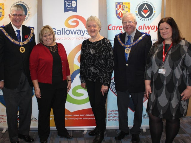 Photo shows Leader of West Lancashire Freemasons Tony Harrison with partially sighted service users Linda McCann, from Preston, and Laurel Devey and Nicola Hanna. They are stood in front of a banner which says Galloway's