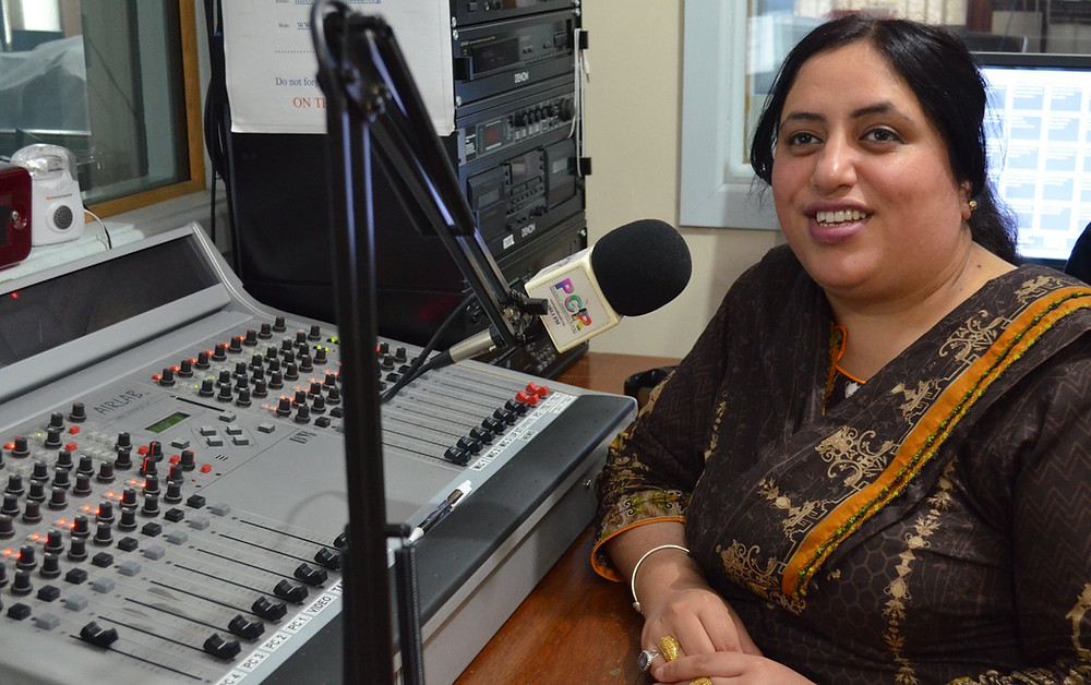 Photo shows Saima sat in front of her mixing desk in the radio studio. To her left is a large microphone