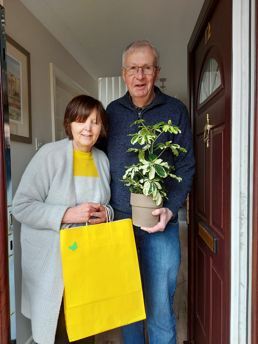 Sue is holding a yellow gift bag and Peter is holding a plant