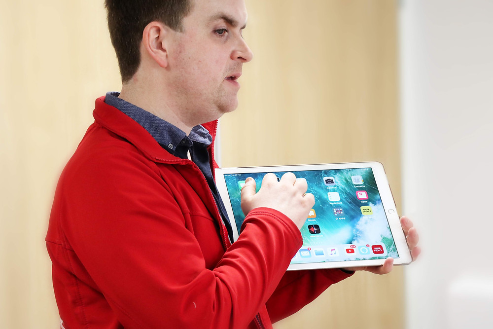 Photo shows Andrew holding a large Tablet. He is wearing a red Galloway's top