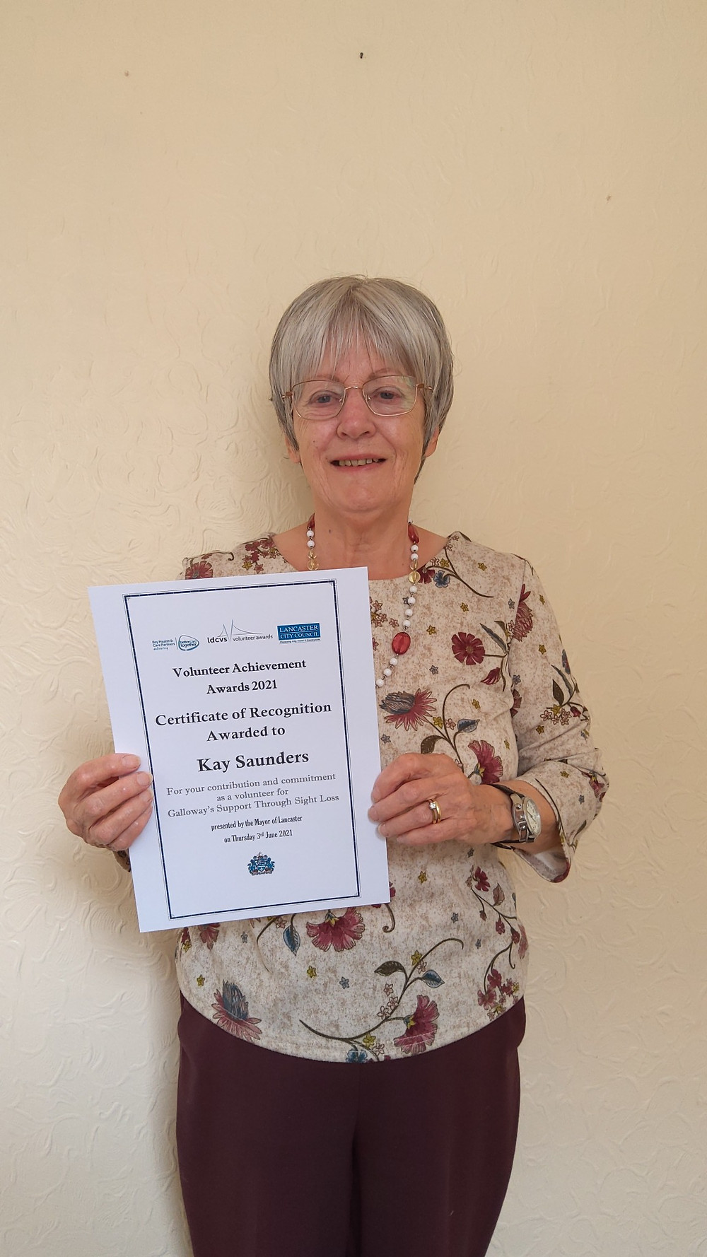 Kay is stood against a white wall holding her certificate