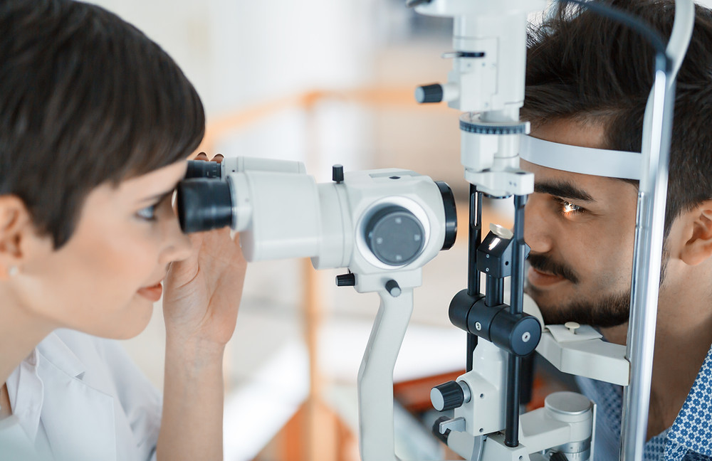 Photo shows a female optician looking into a patient's eyes using specialist equipment