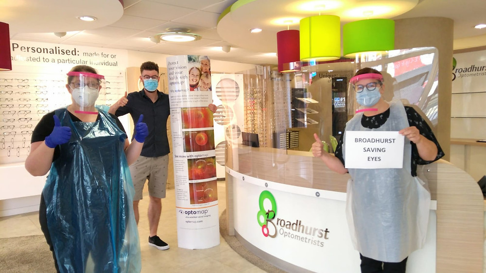 Three memebers of staff wearing plastic aprons, glasses, face masks and plastic visors stand socially distant frm each other. They are stood inside the optometrists, witth glasses in the background, One woman, to the right is holding a sign saying Broadhurst Saving Eyes