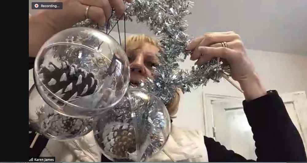 Photo shows a Zoom screen with Karen James holdig up three baubles with pine cones inside and silver tinsel