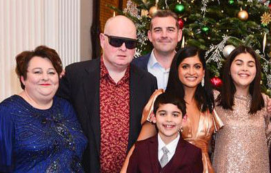 Penny and Nigel Walker, Alistair and Tamara Grant with their two children Max and Eleanor. Theyare stood in front of a Christmas tree. Penny is wearing a blue dress with beads, Nigel is wearing a red patterned shirt, black jacket and dark glasses. Alistair is wearing a white shirt and dark jacket. Tamara is wearing a gold jumpsuit. Max is wearing a white shirt, gtey tie and maroon jacket. Eleanor is wearing a sparkly light pink dress.